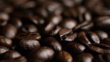 colpo rotante di deliziosi chicchi di caffè tostati su una superficie bianca - chicchi di caffè 024