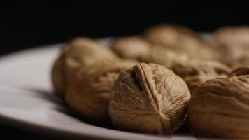 film, roterande skott av valnötter i sina skal på en vit yta - valnötter 035 video