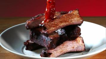 sauce barbecue coulée et éclaboussée au ralenti (1500 images par seconde) sur des côtes de barbecue - bbq phantom 074