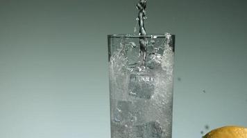 líquido transparente carbonatado que se vierte y salpica en cámara ultra lenta (1,500 fps) en un vaso lleno de hielo - líquido vertido 015