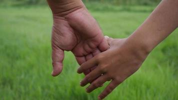 Close up hand of the father holding the daughter hand in slow motion scene