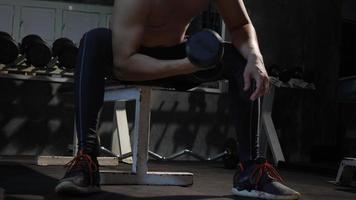 mão de jovem segurando halteres para exercícios na academia video