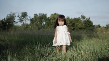 cámara lenta, niña caminando sobre la hierba verde