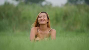 mulher sentada relaxando com os braços levantados no campo de grama