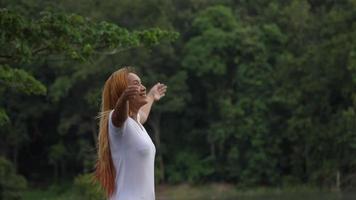 bela jovem em pé com os braços erguidos desfrutar da natureza