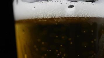 a cerveja está sendo derramada no copo com a espuma deslizando pela lateral do copo video