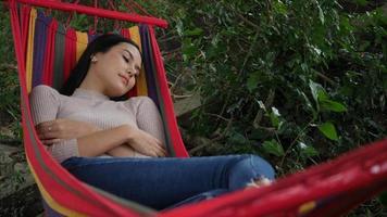 bela jovem deitada para dormir na rede e relaxar video