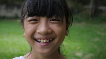 Retrato de niña asiática sonriendo mirar a la cámara