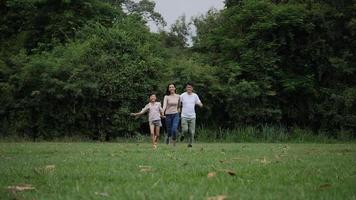Slow motion of parents with daughter running enjoy in the park