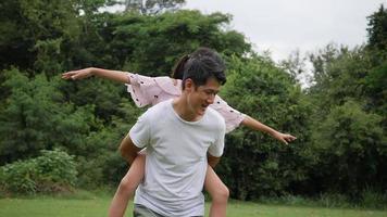 pai carregando a filha nas costas, girando e sorrindo em câmera lenta