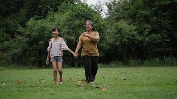 Grandmother with granddaughter walking talk about family in the park