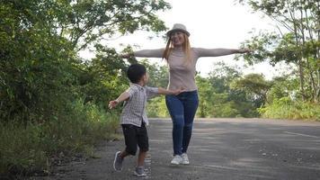 cámara lenta, madre y su hijo corriendo en la calle