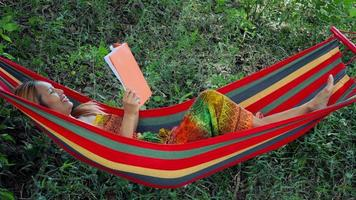 Young woman laying down on hammock and reading a book