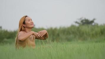 mulher alegre sentada no campo verde e levantando a mão para refrescar a vida
