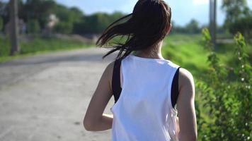 Rücken der jungen schönen asiatischen Frau, die im Park joggt