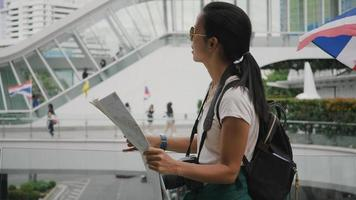 Young tourist woman exploring Thailand map while traveling in Thailand