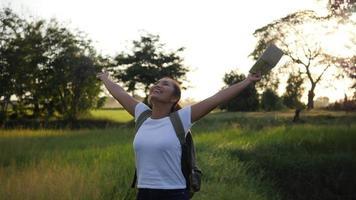 mujer levantando sus manos felizmente mientras camina en la naturaleza