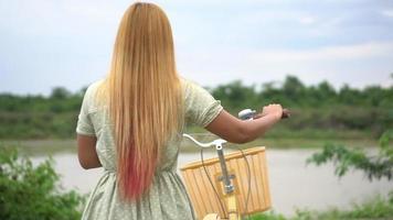mujer joven, con, bicicleta, ambulante, en el parque