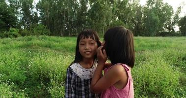 dos niñas susurran contando secretos