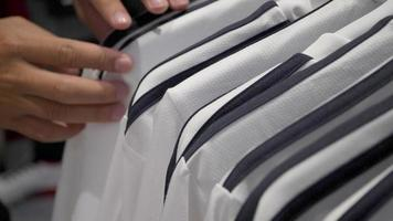 Close up finger of male customer selecting white T-shirts in a shop