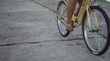 Nahaufnahme der Beine einer aktiven Frau, die Fahrrad im Park fahren