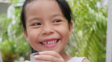 niña bebiendo agua dulce después de jugar