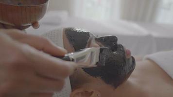 Hermosa joven recibe terapia de spa de carbón video