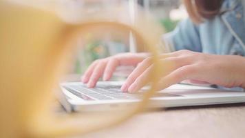 freiberufliche asiatische Geschäftsfrau, die arbeitet, Projekte auf Laptop macht und warme Tasse Kaffee trinkt, während sie auf Tisch im Café sitzt.