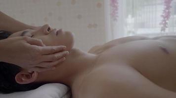 Joven recibiendo masaje facial del terapeuta de spa