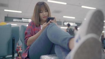 Heureuse femme asiatique en utilisant et en vérifiant son smartphone assis sur une chaise dans le hall du terminal en attendant son vol à la porte d'embarquement à l'aéroport international. video