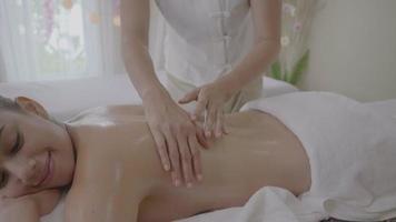 mujeres jóvenes que reciben masaje de espalda en el centro de spa