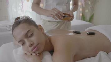 Mujer joven con masaje con piedras calientes en el spa