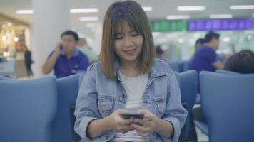 câmera lenta - feliz mulher asiática usando e verificando seu smartphone no corredor do terminal enquanto espera seu voo no portão de embarque no aeroporto internacional. video