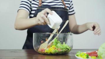 close-up de mulher chefe jovem consciente de saúde jogando uma saborosa salada verde orgânica. video