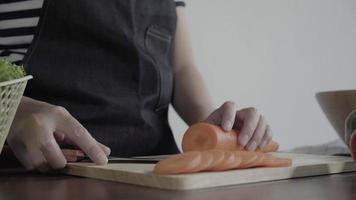 Nahaufnahme der Hauptfrau, die Salat gesundes Essen macht und Karotte auf Schneidebrett in der Küche hackt.