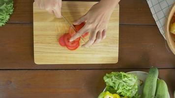 Draufsicht des Frauenchefs, der gesundes Essen des Salats macht und Tomate auf Schneidebrett in der Küche hackt.