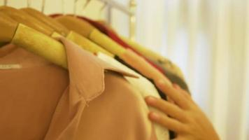 armario de casa o tienda de ropa vestuario. mujer joven asiática eligiendo su ropa de traje de moda en el armario en casa o tienda. chica piensa qué ponerse suéter.