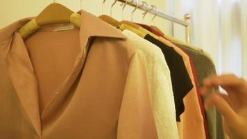 guarda-roupa doméstico ou vestiário da loja de roupas. jovem asiática escolhendo suas roupas de roupa de moda no armário em casa ou na loja. garota pensa o que vestir suéter. video
