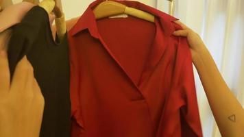 guarda-roupa doméstico ou vestiário da loja de roupas. jovem asiática escolhendo suas roupas de roupa de moda no armário em casa ou na loja.