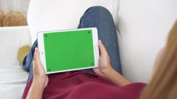 Young asian woman using black tablet device with green screen. video