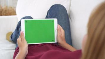 Young asian woman using black tablet device with green screen.