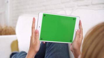 junge asiatische Frau, die schwarzes Tablettengerät mit grünem Bildschirm verwendet.