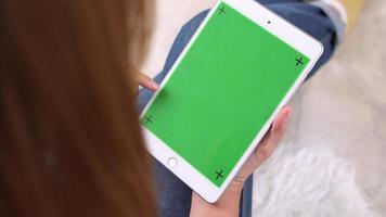 jovem mulher asiática, usando o dispositivo tablet preto com tela verde.