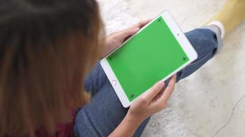 jovem mulher asiática, usando o dispositivo tablet preto com tela verde. video