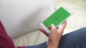 junge asiatische Frau, die weißes Smartphone-Gerät mit grünem Bildschirm verwendet.