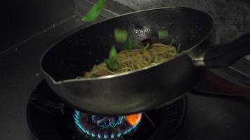 cámara lenta - chefs está preparando y cocinando espaguetis en la cocina de un restaurante. video