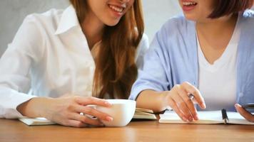 mulheres de negócios usam telefone celular e escrever relatório na mesa de madeira. mulher asiática usando telefone e café. freelancer trabalhando em uma cafeteria. woking fora do estilo de vida do escritório. video