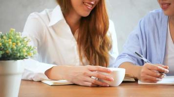 Las empresarias utilizan el teléfono móvil y escriben un informe sobre la mesa de madera. mujer asiática con teléfono y taza de café. autónomo que trabaja en cafetería. woking fuera del estilo de vida de la oficina.