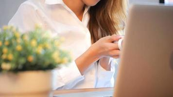 Young business women drinking coffee sitting at table in cafe. Asian woman using laptop and cup of coffee. Freelancer working in coffee shop. Working outside office lifestyle.