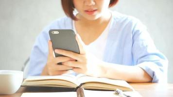 empresaria utilizar teléfono móvil y escribir un informe sobre la mesa de madera. mujer asiática con teléfono y taza de café. autónomo que trabaja en cafetería. woking fuera del estilo de vida de la oficina.